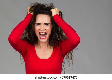 A very frustrated and angry woman is pulling her hair and screaming.