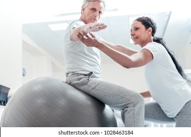 Very good. Determined old wrinkled grey-haired man sitting on a ball for exercises and a pretty young dark-haired afro-american woman helping him to train his arms while kneeling