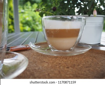 Very good fresh hot coffee in a transparent cup. Cappuccino or white coffee for a business meeting with a client in a garden.
