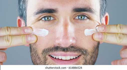 A very handsome man smiles and puts the face cream and eye contour anti-wrinkle and anti-aging for the care of his body and knows beauty. Concept: beauty, cream, beauty