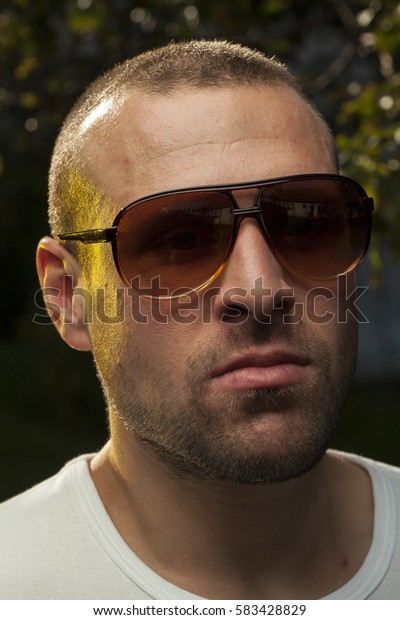 Very handsome man wearing sunglasses, looking at the camera