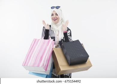 Very happy beautiful Arabic young woman wearing abaya and hijab with shopping bags, Arab shopping concept.
