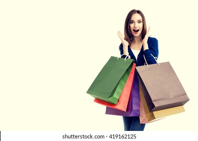 Very happy beautiful young woman in casual clothing with shopping bags, with copyspace for slogan or text message