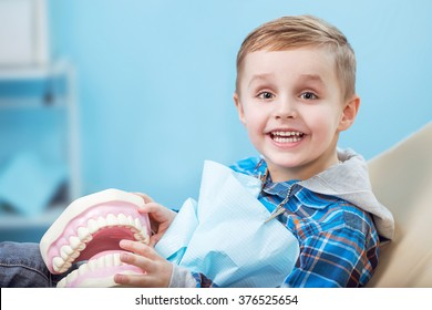 very happy boy after the doctor at the clinic, holding a dental  jaw in her hands and have a beautiful white smiles. Copy space