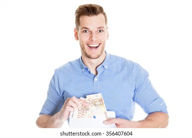 Very happy businessman holding money in envelope over white background