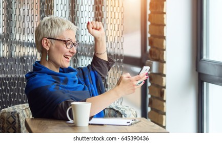Very happy businesswoman celebrating good news. Woman sitting in a cafe received a good message while reading in her phone.