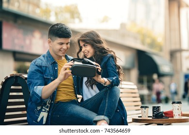 A very happy couple uses a pair of VR glasses to interact with virtual reality sitting on a terrace and having a coffee. They laugh in laughter and have fun with the eyewear model for virtual reality