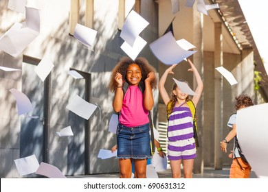 Very happy girl smiling throwing papers in the air