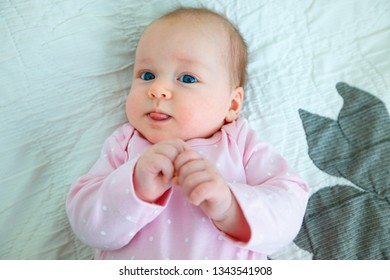 Very happy laughing baby girl in pink body suit lying on her back on the blanket and showing her tongue