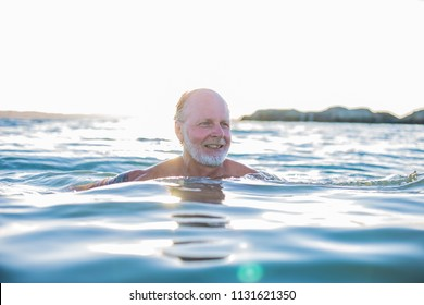 A very happy middle aged man swimming in the ocean, the west coast, Sweden