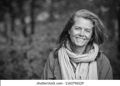 A very happy middle aged woman, outside in the nature, Sweden