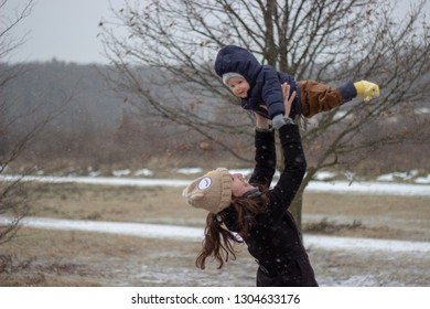 very happy mother is catching her flying little adorable cute babyboy son above her head with snowy landscape in the background