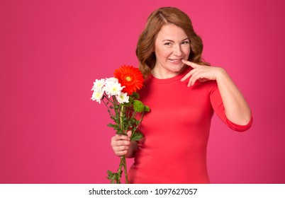 Very happy woman. Beautiful adult woman with flowers on a pink background.