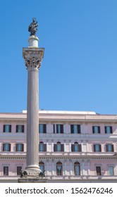 A very high corinthian  column with Madonna and the child on the top, a nice building in the background