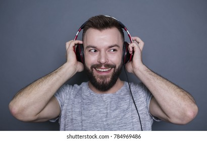 Very high quality sound. Beautiful modern smiling boy in big headphones listening to music on a gray background.