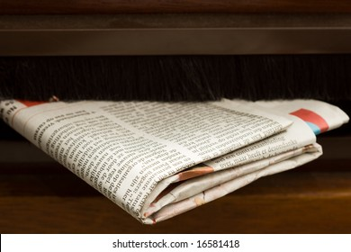 Very high resolution close-up shot of newspaper coming in the mail box in a wooden door.