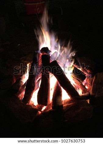 A very hot and beautiful campfire/bonfire to huddle around and roast marshmallows. See the intensity of the fire with the various colors of white, blue, purple, yellow and the red/orange embers.