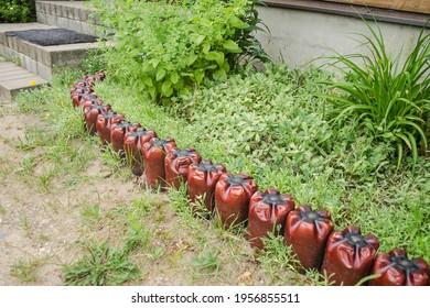 Very interesting flowerbed fence, made of brown two - liter plastic bottles, Kraslava, Latvia.