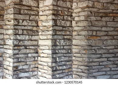 Very interesting and unique exterior wall of stone building, with different sections jutting out from others.