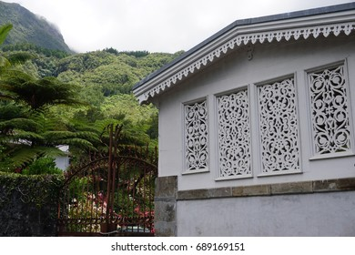 Very intricate metal work on the windows and roof edge of a typical house in the tropical mountains of La Reunion, France