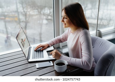 Very joyful woman holding credit card and using laptop computer. Online shopping concept. Payment Transaction at Computer using Credit Card
