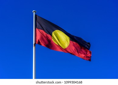 A very large Aboriginal flag on a white flagpole against a blue sky background