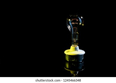 A very large antique lightbulb with the filament powered on low to show the bulb dimly lit.  Use for an idea symbol with room for text on the black background.