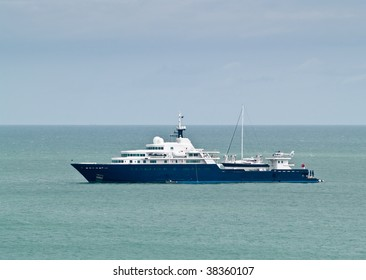 Very large blue private yacht anchored in bay