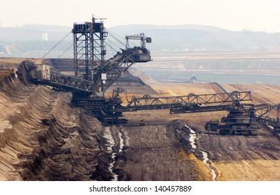 A very large bucket-wheel excavator and conveyor belt in a brown-coal mine