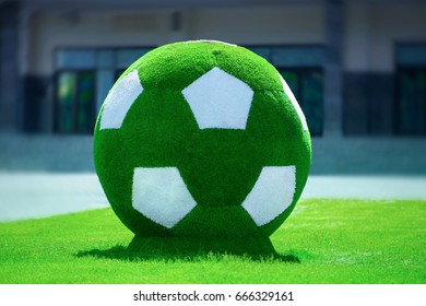 A very large green soccer ball made of grass for fans and tourists in Russia.