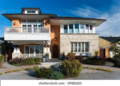 A very large house squeezed between two small houses.