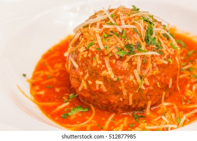 A very large Italian meatball bathed in rich pomodoro sauce, garnished with parmesan and parsley