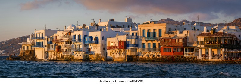 "Very large panoramic view at high resolution huge print of the ""Little Venice"" part of the town of Mykonos, Greece, with unidentified people having dinner while watching the beautiful sunset light."