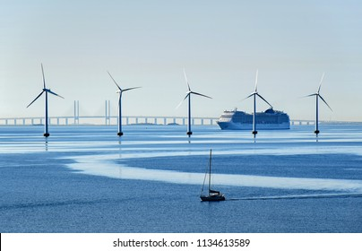 A very large passenger ship and a small sailboat pass offshore wind turbines near the Oresund Bridge between Denmark and Sweden