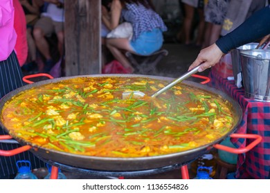 A very large seafood curry being cooked at an open air market.