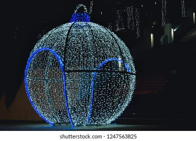 A very large and walkable Christmas ball as a decoration for the Christmas season with many fairy lights and a blue luminous border.