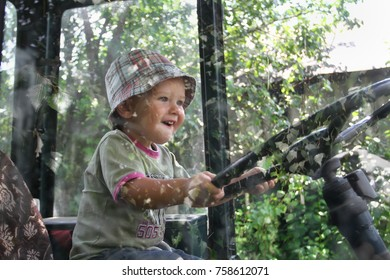Very little white boy in a plaid Panama sits behind the wheel of the tractor. baby like to sit in my father's cab and turn the steering wheel.