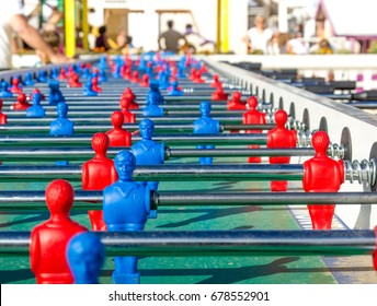 Very long foosball table to play soccer with red and blue players