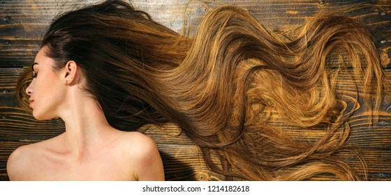 Very long hair on wooden background. Beautiful model with curly hairstyle. Hair Salon concept. Care and hair products