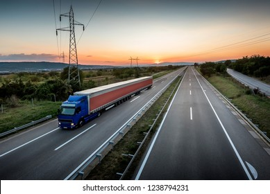 Very long lorry truck on the highway road through the countryside at sunset