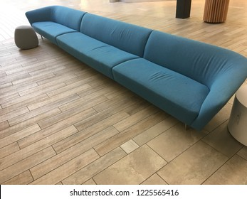 Very long modern contemporary couch with light brown wooden flooring in well lit interior setting