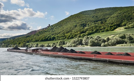 Very long, red barge moves coal up the Rhine River with a castle in the background.  Bacarach area, Germany. August 2019.