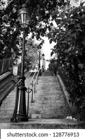 A very long staircase with an old street lamp in Montmartre, Paris, France. Black and white