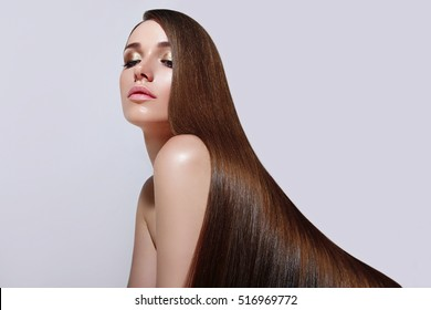 Very long, straight silky hair. The girl with long ringlets. Keratin straightening. Makeup, beauty, cosmetics for hair, silky hair, hairstyle, long hair, brown-haired, advertising.