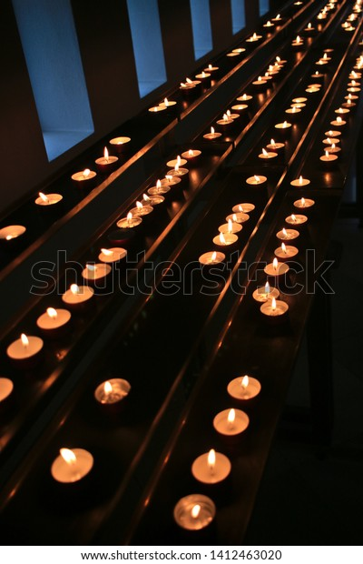 Very many small candles arrayed on long tables symbolizing prayers for decedents