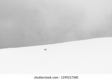 A very minimalistic view of two distant people over a mountain covered by snow