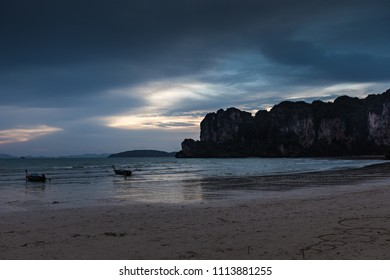 A very moody sunset over Krabi beach with mountains and boats in the scene.