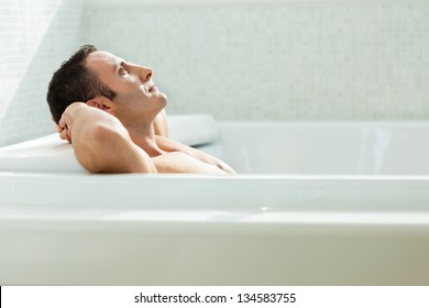 a very muscular and fit man relaxing in a luxury bathtub
