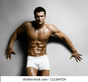 the very muscular handsome sexy guy on dark  grey background, naked torso