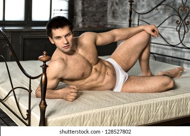 the very muscular handsome sexy guy lie on bed  in  bedroom